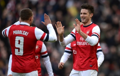 Arsenal's Giroud celebrates with teammate Podolski after Giroud scored a goal during their FA Cup fourth round soccer match against Brighton and Hove Albion in Brighton